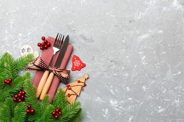 Hoogste mening van vork en mes op servet met kerstmisdecoratie en nieuwe jaarboom op cement, vakantie en feestelijk concept