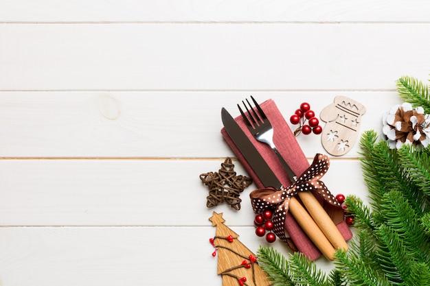 Hoogste mening van vork en mes op servet met kerstmisdecoratie en nieuwe jaarboom op houten, vakantie en feestelijk concept