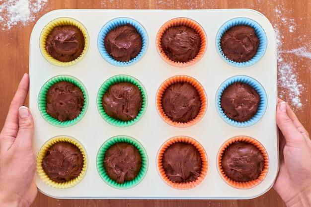 Hoogste mening van vrouwelijke handen die bakseltray met ruw chocoladedeeg houden in kleurrijke document koppen
