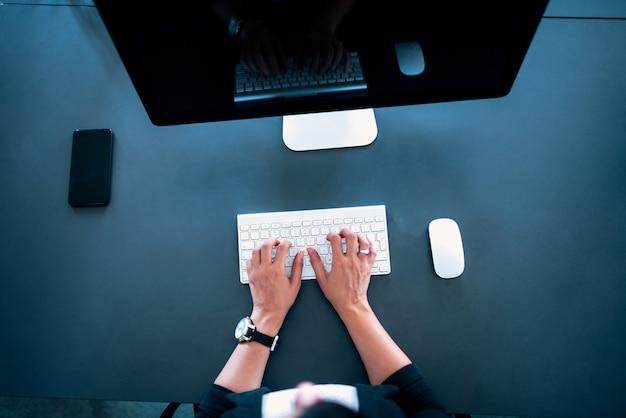 Hoogste mening van vrouwelijke handen die op draadloos toetsenbord typen.