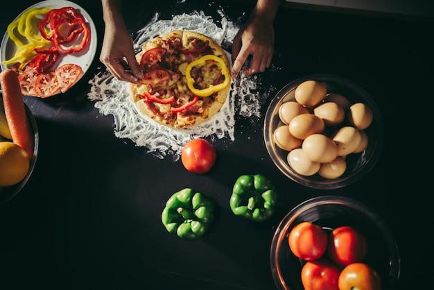 Hoogste mening van vrouwenhand gezet bovenste laagje op eigengemaakte pizza.