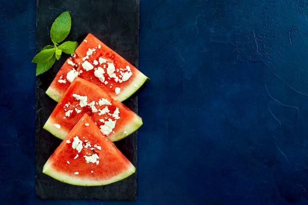 Hoogste mening van watermeloenplakken op blauwe achtergrond
