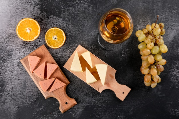 Hoogste mening van wijnglas en kaas op houten scherpe raad op donkere horizontaal