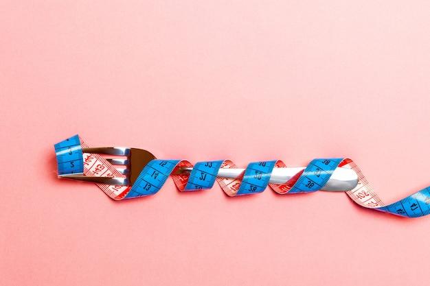 Hoogste mening van zwaarlijvigheidsconcept met vork die in het meten van band op blauw wordt verpakt