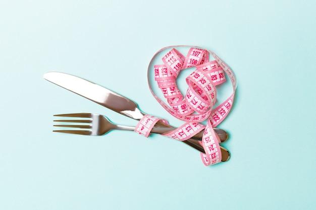 Hoogste mening van zwaarlijvigheidsconcept met vork en mes dat in gekrulde metende band op blauw wordt verpakt