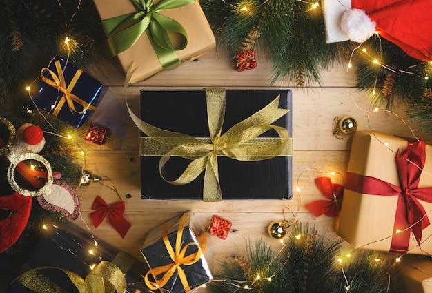 Hoogste mening van zwart goud huidig tussen kerstmisornament op houten textuur