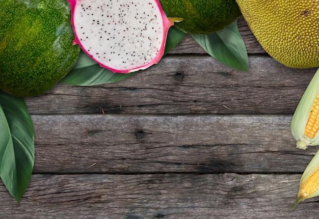 Hoogste meningen van houten bureau met fruit, tropische bladeren en lege ruimte voor achtergrondontwerp