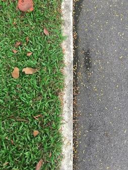 Hoogste menings groene die gras en asfaltweg door witte concrete lijnen wordt gescheiden