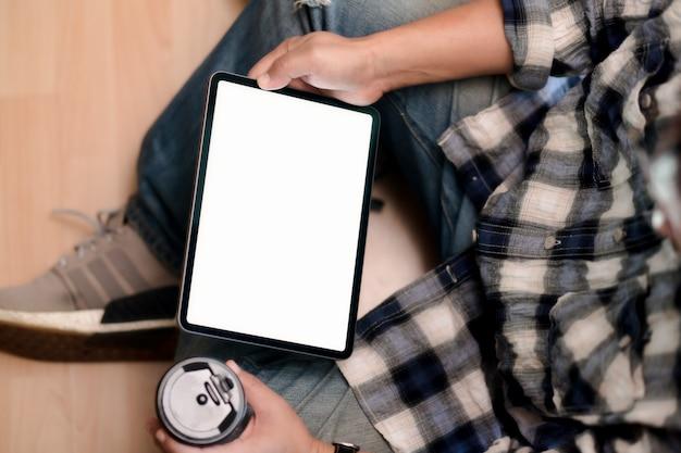 Hoogste menings jonge mens die tablet gebruiken terwijl het zitten op de vloer.