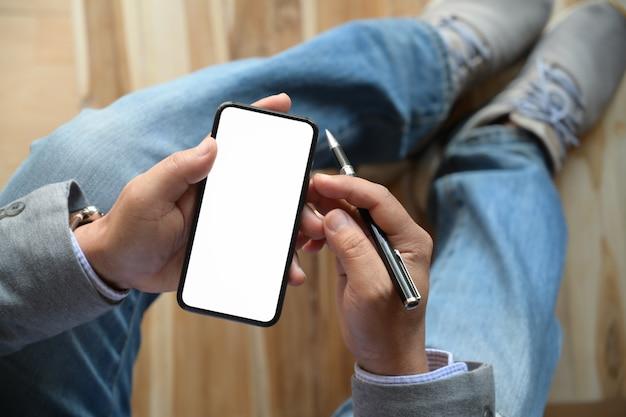 Hoogste menings mannelijke handen die smartphone gebruiken bij vage achtergrond.