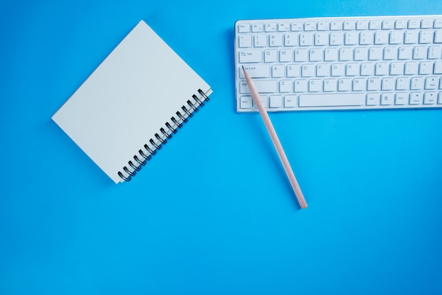 Hoogste menings open notitieboekje, potlood op blauw bureau