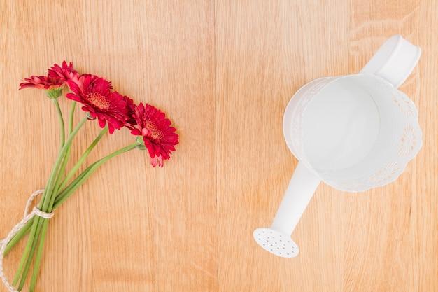 Hoogste menings rode bloemen en gieter op houten achtergrond