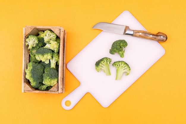 Hoogste menings verse broccoli in houten doos dichtbij scherpe raad met mes op gele oppervlakte