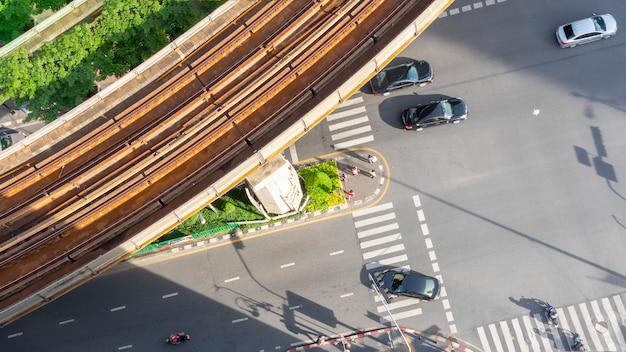 Hoogste meningsantenne van een drijfauto op asfaltspoor en voetzebrapad in verkeersweg met licht en schaduwsilhouet met de trein van de spoorhemel.