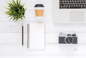Hoogste meningsbeeld van open notitieboekje met blanco pagina's en laptop op houten lijst