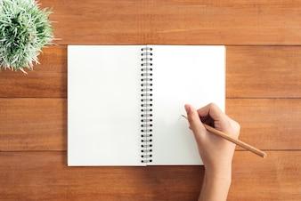 Hoogste meningsbeeld van open notitieboekje met blanco pagina's op houten lijst. klaar om tekst of mockup toe te voegen