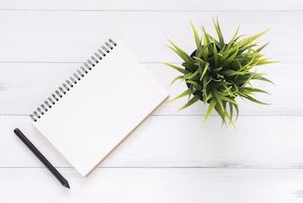 Hoogste meningsbeeld van open notitieboekje met blanco pagina's op houten lijst
