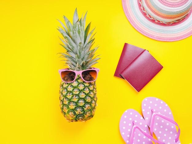 Hoogste meningsbeeld van twee paspoorten, verse ananas die zonnebril, strandpantoffels en hoed op een gele achtergrond dragen.