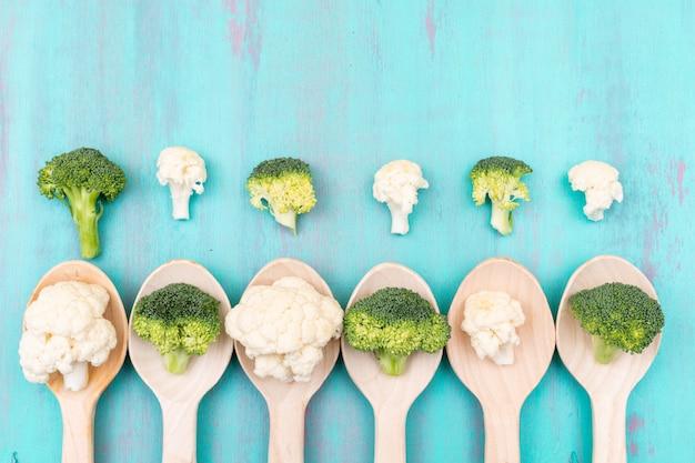 Hoogste meningsbloemkool en broccoli in houten lepel op blauwe oppervlakte