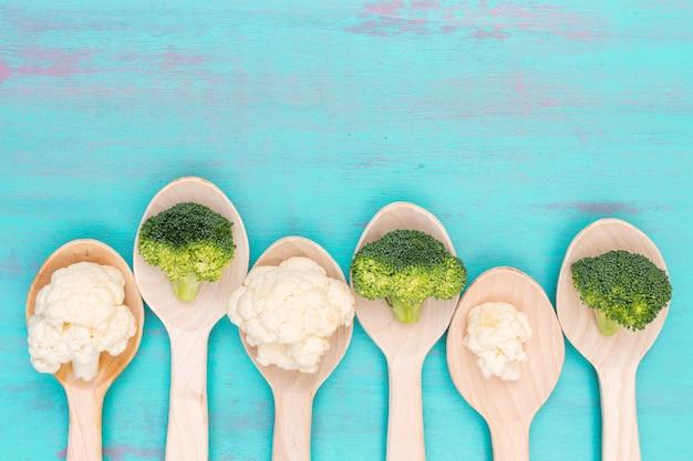 Hoogste meningsbloemkool en broccoli in houten lepels met exemplaarruimte op blauwe oppervlakte