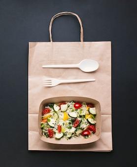 Hoogste meningsdoos met salade op zwarte achtergrond