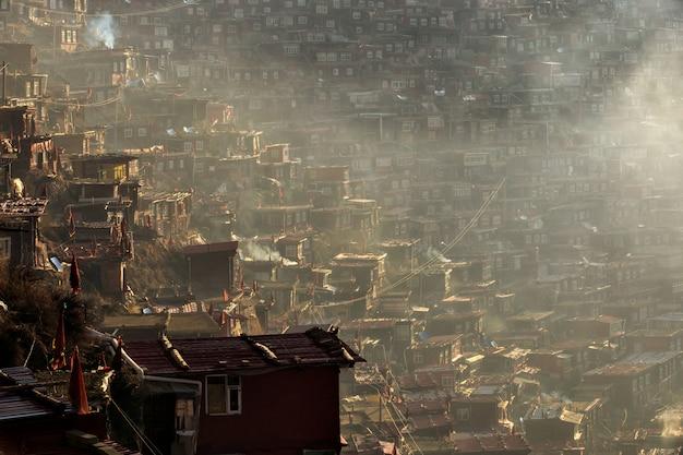 Hoogste meningsklooster in larung-gar (boeddhistische academie) in een warme en mistige ochtendtijd, china