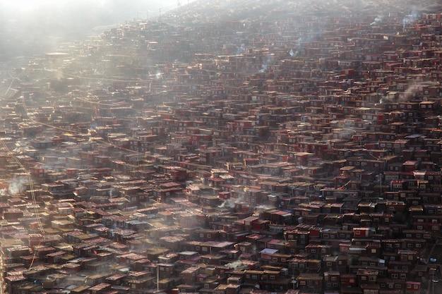 Hoogste meningsklooster in larung-gar (boeddhistische academie) in een warme en mistige ochtendtijd, sichuan, china