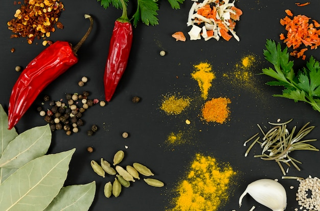 Hoogste meningskruiden en spaanse pepers op zwarte achtergrond