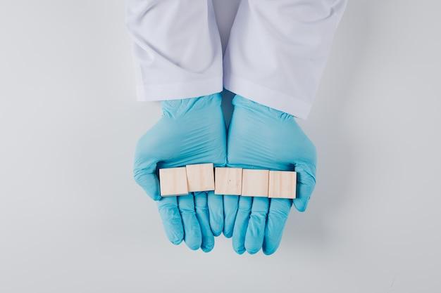 Hoogste meningsmens die in handschoenen houten blokken in beide handen op wit houden
