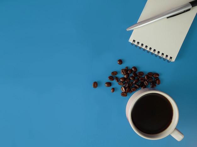 Hoogste meningsnotitieboekje, pen en een kop van koffie op blauw bureau met exemplaarruimte