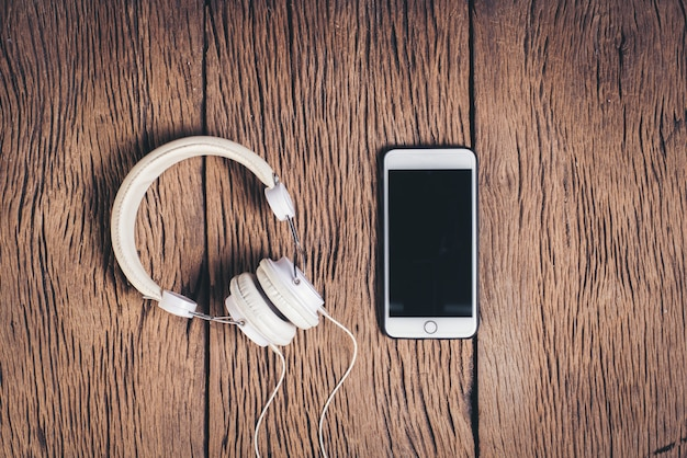 Hoogste meningstelefoon en hoofdtelefoon houten achtergrond