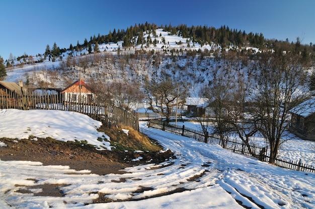 Hooibergen en een schutting van hout, winterlandschap, plattelandsleven, rust in de bergen in het dorp