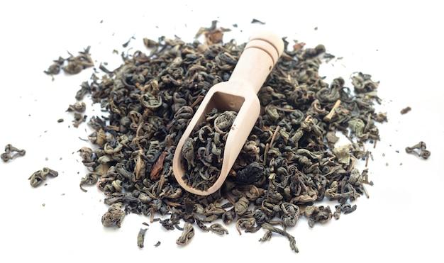 Hoop droge groene thee met geïsoleerde bamboelepel
