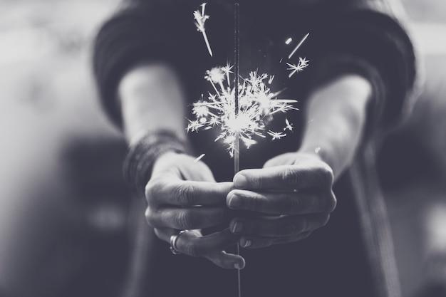 Hoop en geloof concept met vuur licht sterretje dat door vrouwenhanden wordt genomen en vooraan wordt weergegeven - zwart-wit feest romantisch concept - close-up vonklicht met handen - concept van menselijke vrijheid