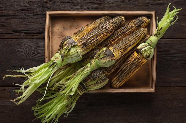 Hoop gegrilde maïs op een houten tafel, bovenaanzicht