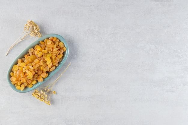Hoop gele rozijnen in bord met gedroogde bloemen op stenen tafel.