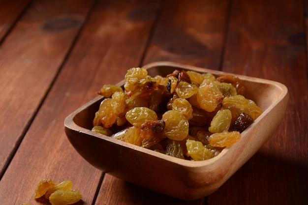 Hoop gele rozijnen, in een houten kom. kom met gedroogde gouden rozijnen. gedroogde druiven.