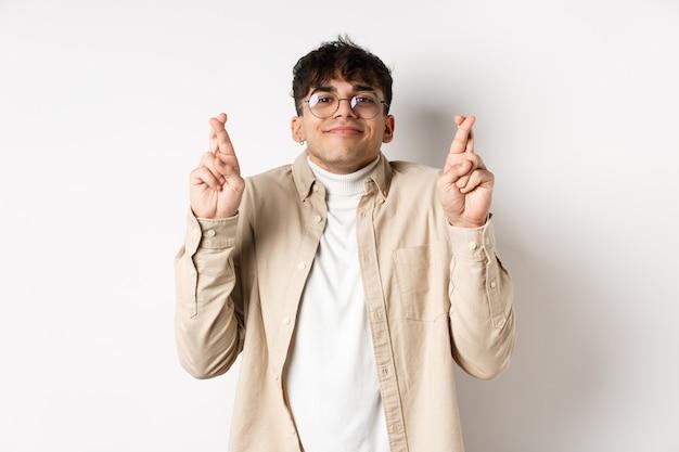Hoop. gelukkige jonge man die wens doet en glimlacht, hoopvol naar de camera kijkt terwijl hij wacht op een droom die uitkomt, vingers kruist voor geluk, staande op een witte achtergrond