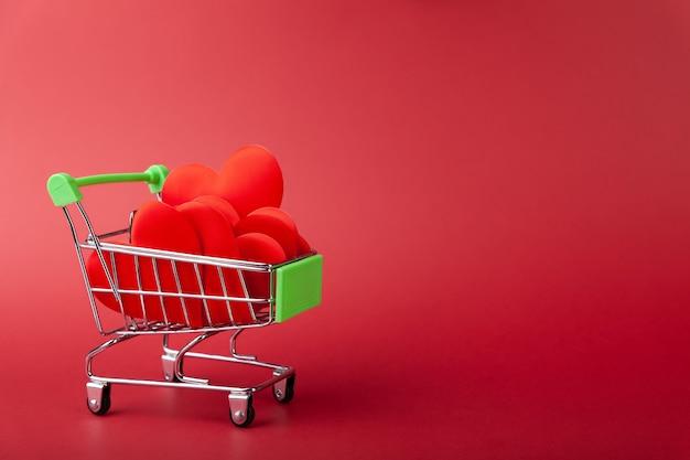 Hoop harten in mini kruidenierswinkelwagentje, op rode muur, verkoop en liefdeconcept, valentijnsdag, exemplaarruimte, horizontaal, zijaanzicht