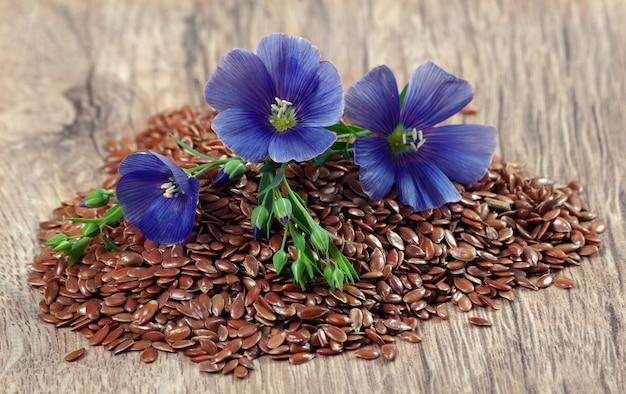 Hoop lijnzaad op een houten tafel. vlasbloemen en droog lijnzaadclose-up