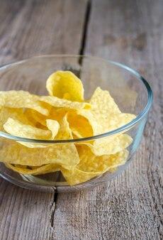 Hoop maïs chips in de glazen kom op de houten tafel