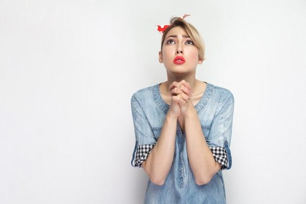 Hoop op hulp of vergeving. portret van een hoopvolle mooie jonge vrouw in een casual blauw shirt en een rode hoofdband die staat en omhoog kijkt en bidt. indoor studio opname, geïsoleerd op een witte achtergrond.