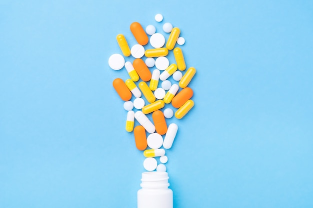 Hoop pillen en capsules die uit een plastic fles morsen. bovenaanzicht - afbeelding