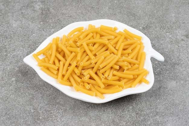 Hoop rauwe macaroni op een witte plaat