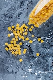 Hoop rauwe pipet rigate pasta in een glazen pot met peperkorrels en knoflook.