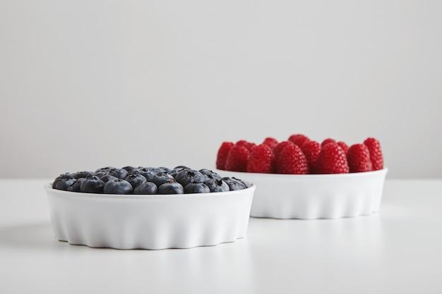 Hoop rijpe frambozen en bosbessen nauwkeurig geplaatst in keramische kommen geïsoleerd op een witte tafel