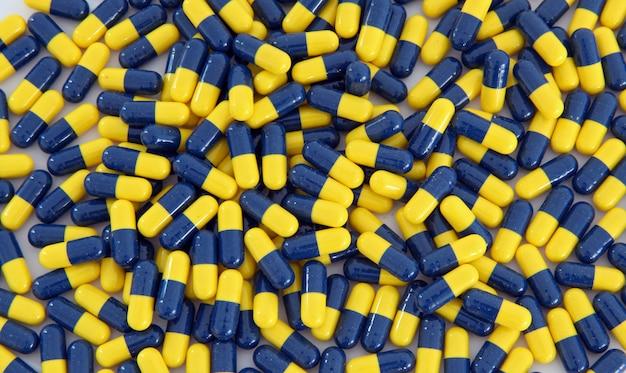 Hoop van blauwe gele capsuleachtergrond