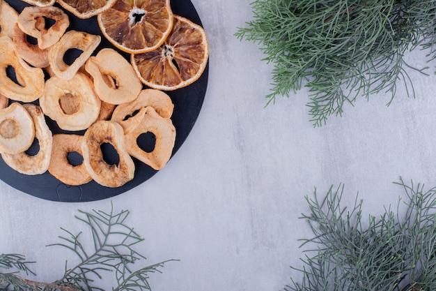 Hoop van gedroogde appel en stukjes sinaasappel op een klein dienblad op witte achtergrond.
