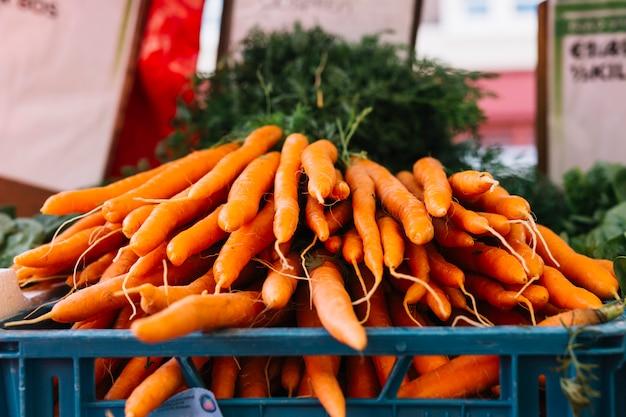Hoop van geoogste wortelen in krat