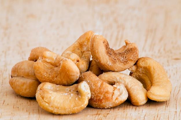 Hoop van geroosterde cashewnoten op een oude houten tafel.